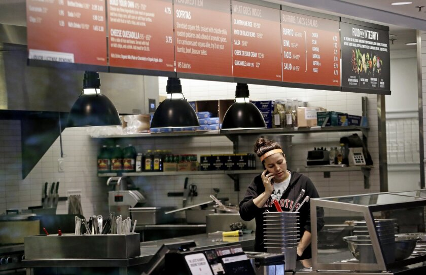 A woman talks on the phone as she stands in the kitchen area of a closed Chipotle restaurant, Monday, Nov. 2, 2015, in Seattle. An E. coli outbreak linked to Chipotle restaurants in Washington state and Oregon has sickened nearly two dozen people in the third outbreak of foodborne illness at the po