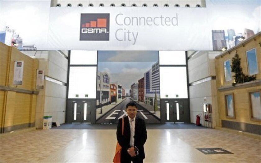 In this Tuesday, Feb. 26, 2013, photo, a man stands up in front of a banner of Connected city at the Mobile World Congress, the world's largest mobile phone trade show, in Barcelona, Spain. The first wave of the wireless revolution was getting people to talk to each other through cellphones. The se