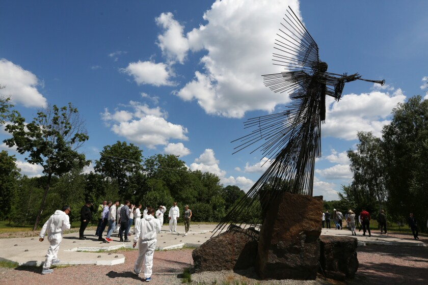 A group of foreign tourists visits the Wormwood Star Memorial in the Chernobyl Exclusion Zone.