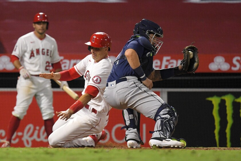 Angels' Jason Castro scores on a double by Brian Goodwin as Seattle Mariners catcher Joseph Odom takes a late throw.