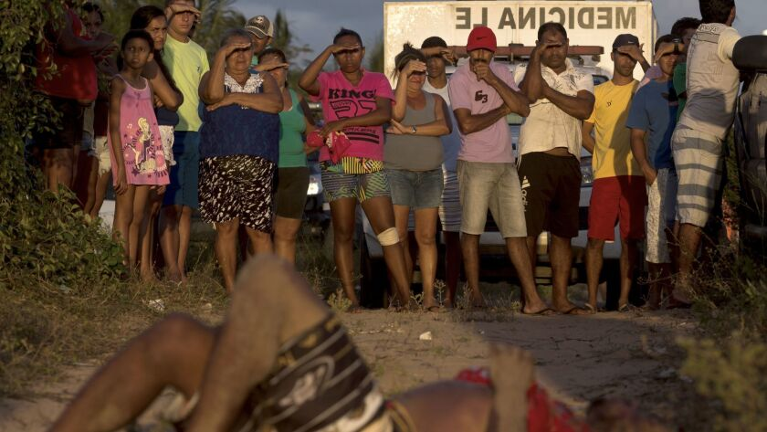 Residents look at the body of a man killed during a confrontation between Sindicato do Crime and Pri