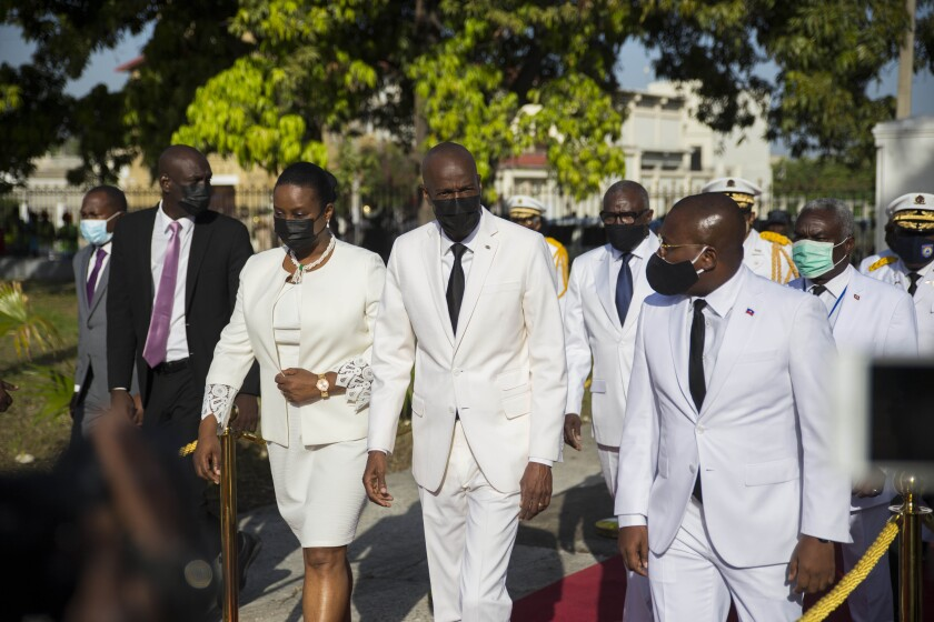 FILE - In this May 18, 2021 file photo, Haitian President Jovenel Moise, center, walks with first lady Martine Moise, left, and interim Prime Minister Claude Joseph, right, during a ceremony marking the 218th anniversary of the creation of the Haitian flag in Port-au-Prince, Haiti. Moïse was assassinated in an attack on his private residence early Wednesday, and the first lady was shot in the overnight attack and hospitalized, according to a statement from Joseph. (AP Photo/Joseph Odelyn, File)