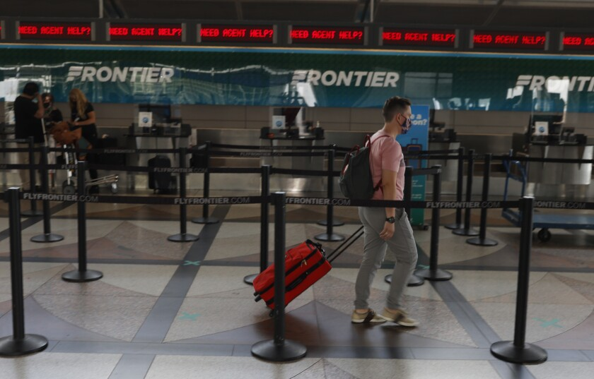 FILE - A lone traveler heads to the ticketing counter of Frontier Airlines in the main terminal of Denver International Airport on July 22, 2020, in Denver. Hotel and home-sharing reservation site Booking.com plans to lay off 25% of its workforce, or more than 4,000 people, due to the impact of the new coronavirus on travel. Connecticut-based parent company Booking Holdings said Tuesday, Aug. 4, that the layoffs will begin next month. (AP Photo/David Zalubowski, File)