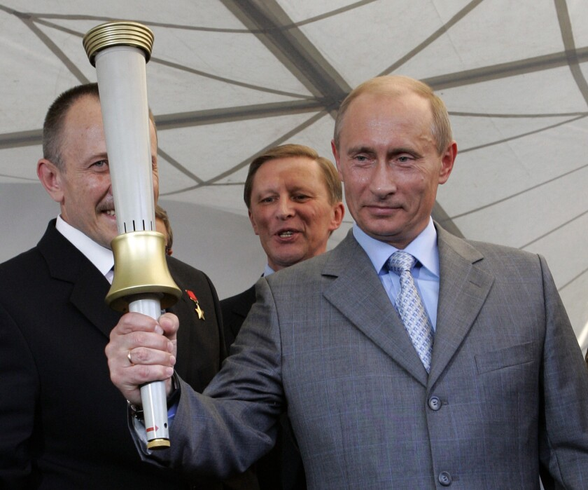 Russian President Vladimir Putin in 2007 holds one of the torches produced for the 1980 Moscow Olympics. Ahead of the Sochi Olympic games this week, more than 200 authors called on the Russian leader to repeal laws that limit freedom of expression.