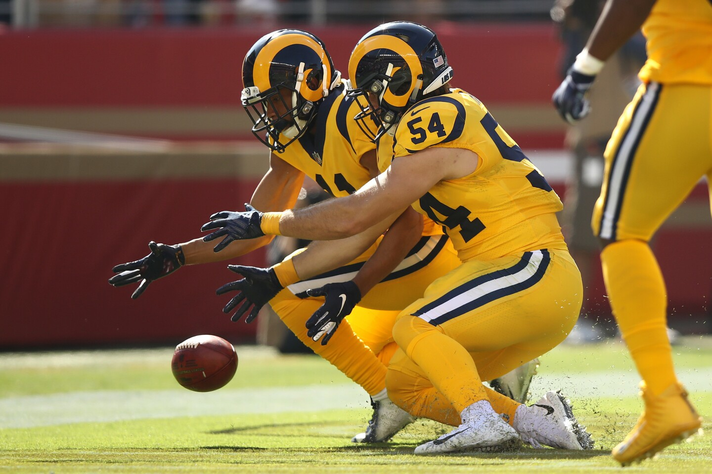 KhaDarel Hodge #11 and Bryce Hager #54 of the Los Angeles Rams dive for a blocked punt in the endzone during their NFL game against the San Francisco 49ers at Levi's Stadium on October 21, 2018 in Santa Clara, California.