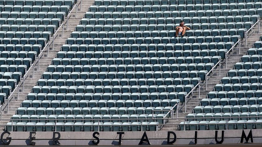A fan sits amid empty seats in the upper deck at Dodger Stadium.
