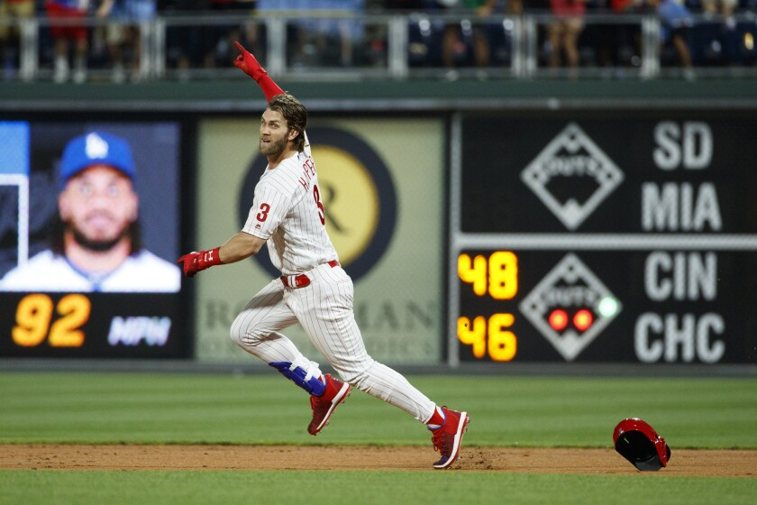 Philadelphia Phillies' Bryce Harper celebrates after hitting a game-winning two-run double off Dodgers relief pitcher Kenley Jansen.