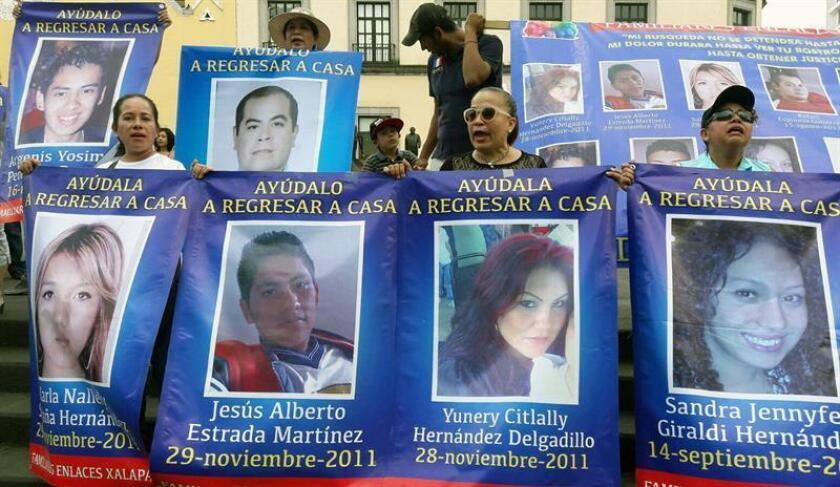 Un grupo de personas exhibe carteles y fotografías de familiares desaparecidos durante una marcha en el estado de Veracruz (México). EFE/Archivo