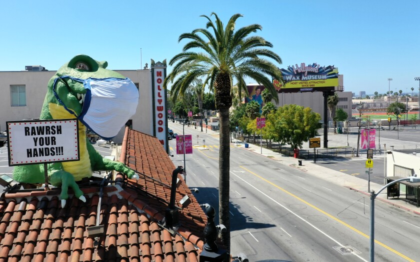 A giant T-Rex wearing a protective mask sends a coronavirus message to a mostly empty intersection of Hollywood Boulevard and Highland Avenue from the top of Ripley's Believe It or Not! Odditorium, which is temporarily closed.