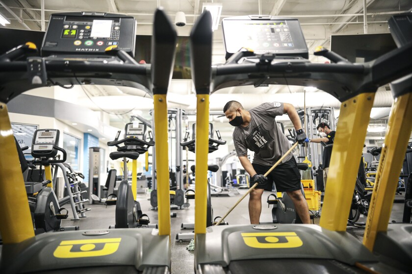 Juan Lopez mops around gym equipment at Chuze Fitness in Chula Vista on Thursday. The gym plans to reopen Saturday.