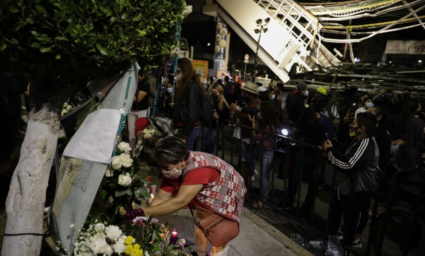 A woman places flowers at a makeshift altar for the people who died in Monday's subway collapse