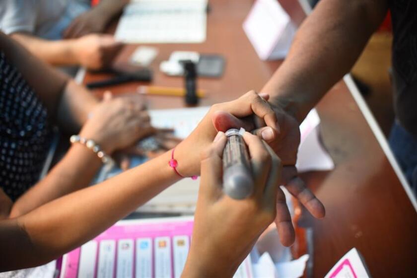 Vista de varios ciudadanos emitiendo su voto. EFE/Archivo
