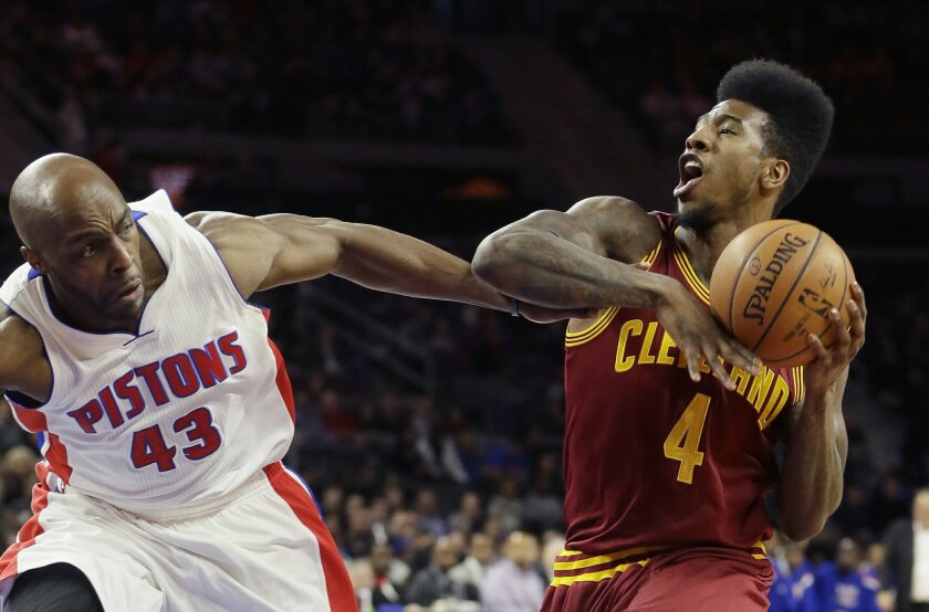Cleveland Cavaliers guard Iman Shumpert (4) is fouled by Detroit Pistons forward Anthony Tolliver (43) during the first half of an NBA basketball game, Tuesday, Feb. 24, 2015 in Auburn Hills, Mich. (AP Photo/Carlos Osorio)