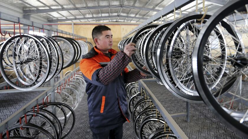 In this Dec. 21, 2018, photo, a staff member works at a factory producing electronic bicycles for ex