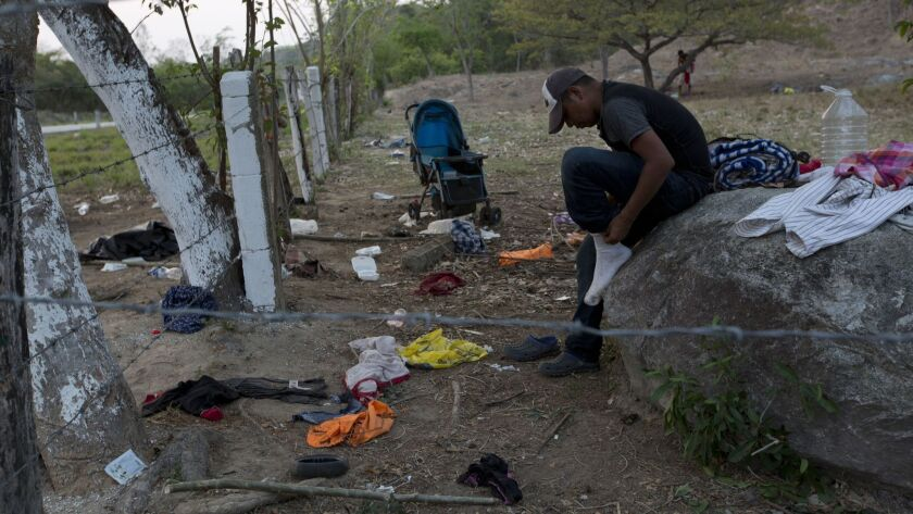 A migrant puts on the socks he'd left behind when his group evaded Mexican immigration agents by run