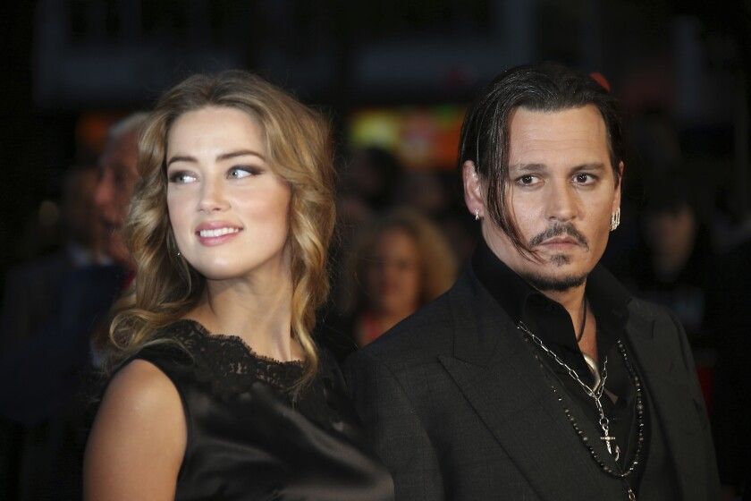 """FILE - In this Oct. 11, 2015 file photo, Amber Heard, left, and Johnny Depp arrive at the premiere of Depp's film """"Black Mass,"""" at the London film festival. Free press advocates in Virginia are concerned that a libel lawsuit between Depp and Heard could set a bad precedent. The Virginia Press Association asked Friday, Nov. 8, 2019 to intervene in a $50 million lawsuit Depp filed against Heard, his ex-wife. Depp says he was defamed by an op-ed piece Heard wrote in The Washington Post in December 2018, in which she never identified Depp by name but referred to herself as a """"public figure representing domestic abuse."""" Depp has denied abusing Heard and said the article clearly refers to earlier abuse allegations Heard made against him. (Photo by Joel Ryan/Invision/AP, File)"""