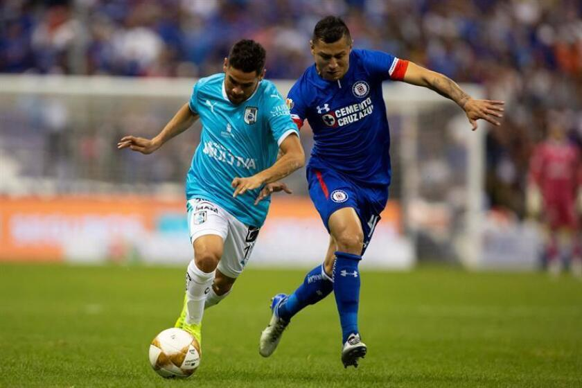 Cruz Azul player Julio Cesar Dominguez (right) marks Queretaro's Daniel Villalva during an Apertura 2018 quarter-final game on Dec. 2, 2018, in Mexico City. EPA-EFE/Francisco Guasco