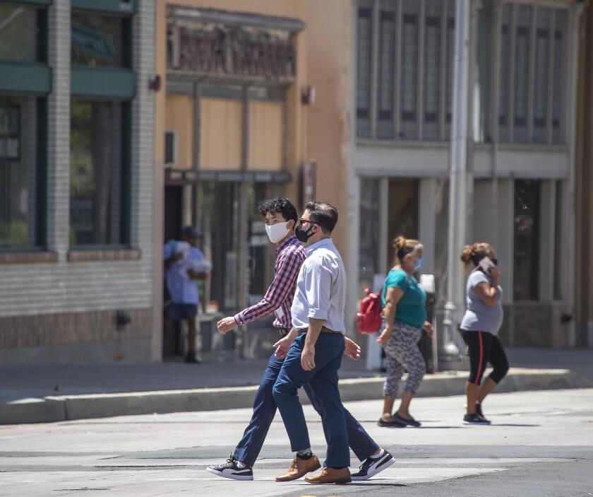 Pedestrians wearing masks cross Main Street on 4th Street in downtown Santa Ana.
