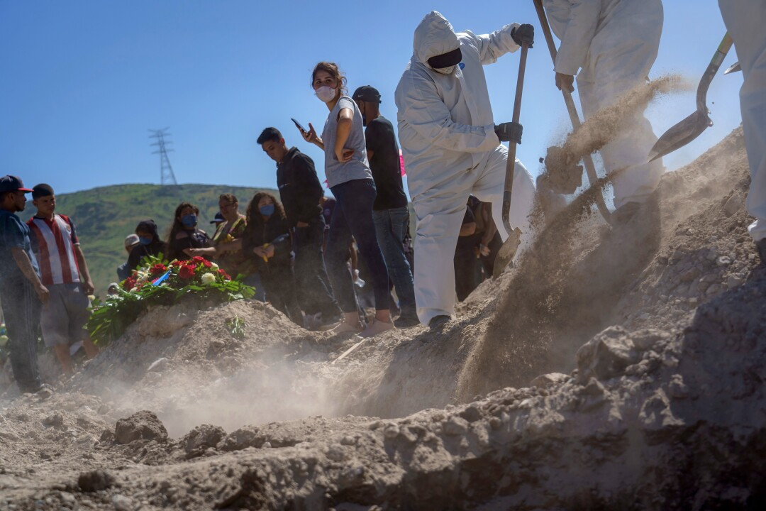 Family members watch as gravediggers in protective suits move from burial to burial at Tijuana's Municipal Cemetery No. 13.