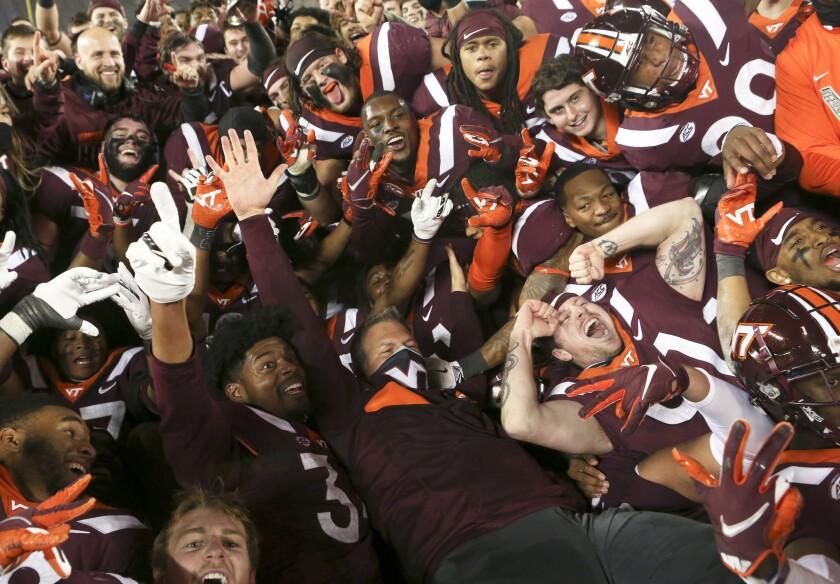 Virginia Tech coach Justin Fuente, center, and his team celebrate a win over Virginia in an NCAA college football game Saturday, Dec. 12, 2020, in Blacksburg, Va. (Matt Gentry/The Roanoke Times via AP, Pool)