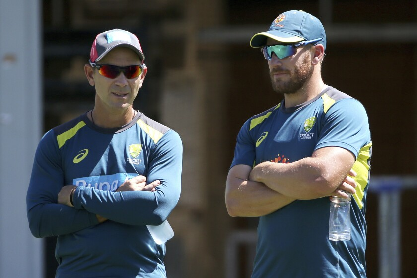 FILE - In this Jan. 1, 2019, file photo, Australia's cricket head coach Justin Langer, left, chats with batsman Aaron Finch during a training session in Sydney. Langer is ready to embrace change to keep his Australian cricket squad on the road as the team prepares to leave Perth on Sunday, Aug. 23, 2020, for England. (AP Photo/Rick Rycroft, File)