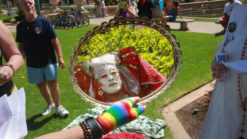 Sister Amanda Reckonwith checks her look in a mirror at a Summer Solstice event hosted by the San Diego Sisters in Balboa Park last month. The San Diego Sisters of Perpetual Indulgence will have a pronounced presence at this weekend's Pride Parade and Festival afterwards. This is the 35th year