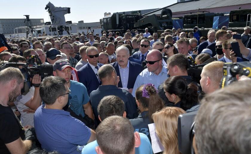 Belarusian President Alexander Lukashenko, center, listens to factory workers in Minsk on Aug. 17, 2020.