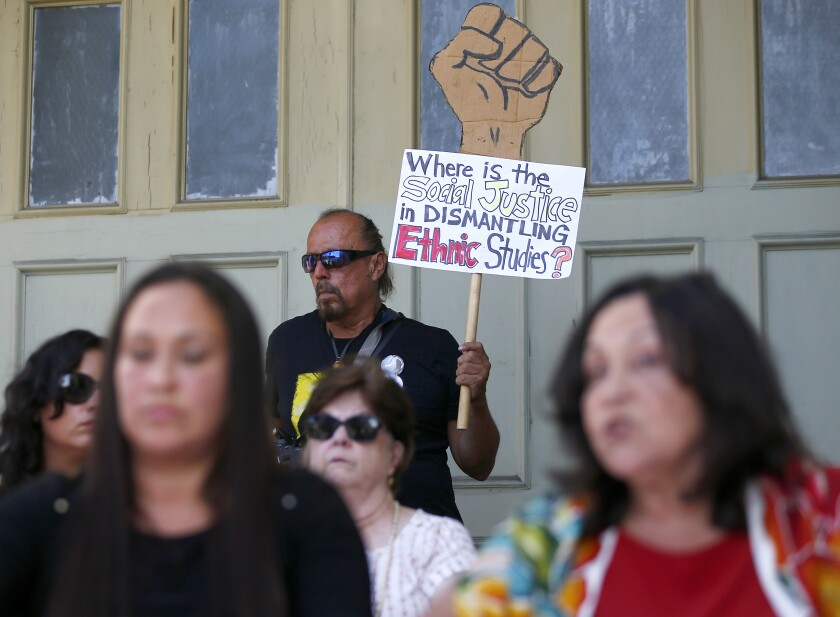 """A man at a rally holds a sign that says, """"Where is the social justice in dismantling ethnic studies?"""""""