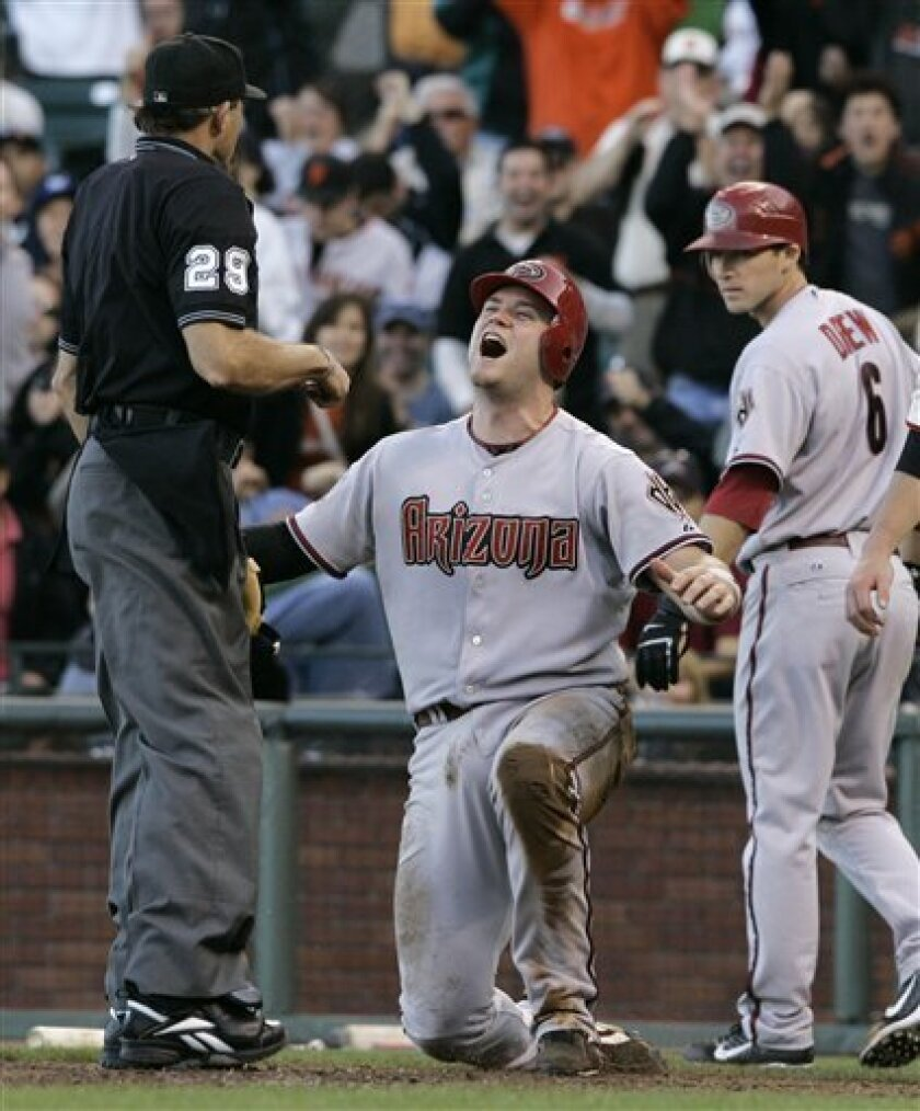 Arizona Diamondbacks' Chris Snyder, center, reacts after home plate umpire Bill Hohn, left, called him out after being tagged by San Francisco Giants catcher Bengie Molina during the fifth inning of their baseball game in San Francisco, Saturday, July 26, 2008. At right is the Diamondbacks' Stephen Drew. Snyder attempted to score from second base after the Diamondbacks' Brandon Webb singled. (AP Photo/Eric Risberg)