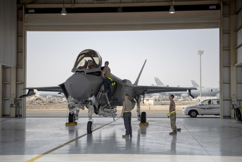 A U.S. fighter pilot and crew members prepare an F-35 for a mission in the United Arab Emirates in 2019.
