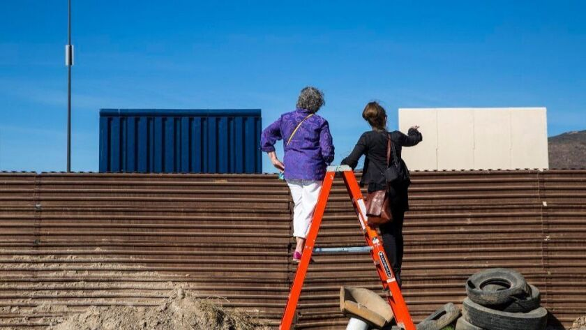 Deborah Joyce of Laguna Beach, left, talks with Nina Magnusdottir during a tour last month to view the border wall prototypes from the Tijuana side. President Trump is scheduled to see the prototypes on Tuesday.