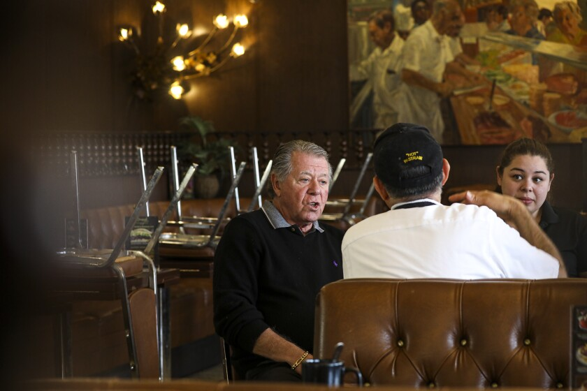Norm Langer, left, owner of Langer's Delicatessen and Restaurant, holds a staff meeting Monday after closing dine-in service for at least two weeks in compliance with an order by Los Angeles Mayor Eric Garcetti aimed at limiting the spread of coronavirus.