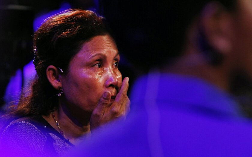 "In this Feb. 12, 2015 photo, Sam Somaly cries as she watches a screen during a reality TV show in Phnom Penh, Cambodia. Somaly sought help finding siblings lost during the brutal Khmer Rouge regime of the 1970s not through the government or an aid agency, but through the reality TV show, ""It's Not"