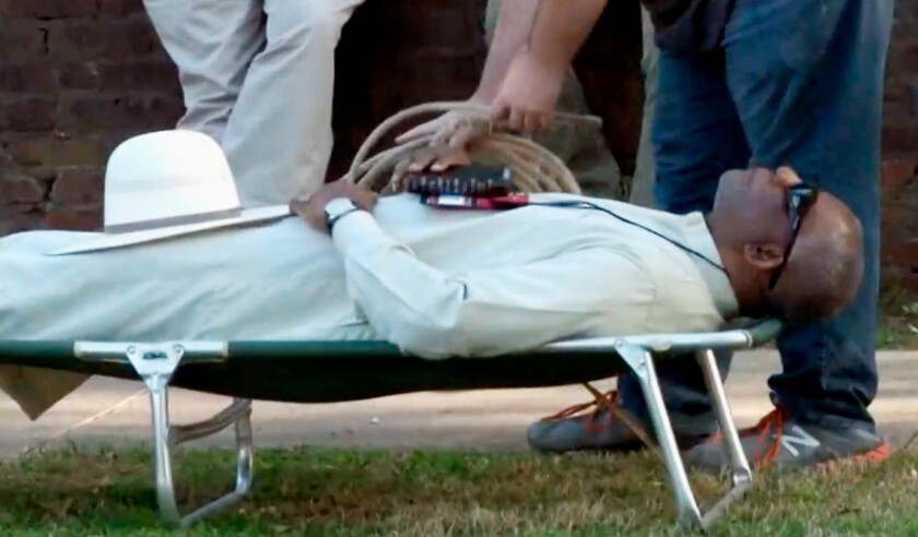 FILE - In this April 17, 2018, file image from video provided by KTHV-TV, a death penalty protester outside the Arkansas governor's mansion in Little Rock prepares to tie rope around Pulaski County Circuit Judge Wendell Griffen who is laying on a cot in protest of executions. The Arkansas Supreme Court says it won't allow a judge who demonstrated against the death penalty the same day he blocked the state from using a lethal injection drugs to resume hearing execution cases. Justices on Thursday, Sept. 19, 2019 rejected the request by Pulaski County Circuit Judge Wendell Griffen, whom the court disqualified from hearing execution cases in 2017 following the demonstration outside the governor's mansion. (KTHV/TEGNA Inc. via AP, File)