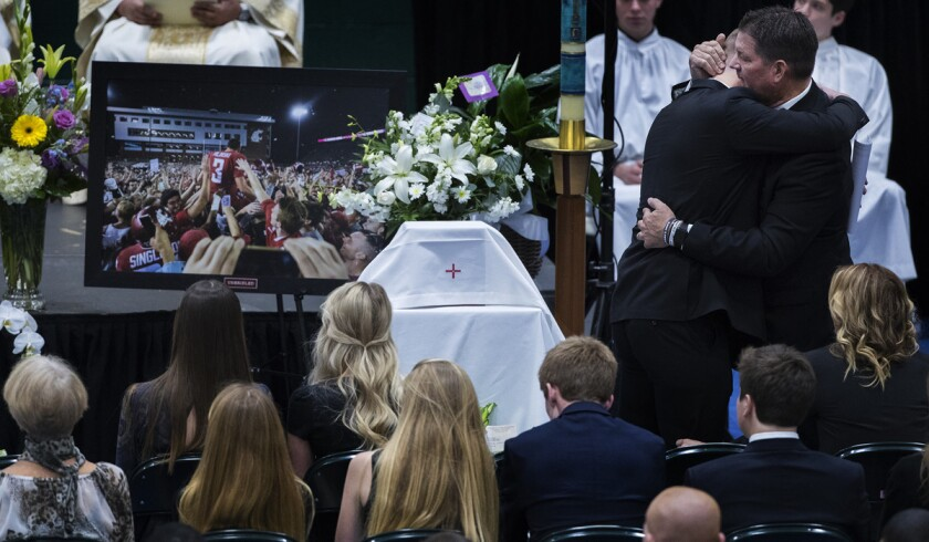 Ryan Hilinski is hugged by his dad Mark Hilinski after speaking at his brother's funeral at Damien High School in January 2018.