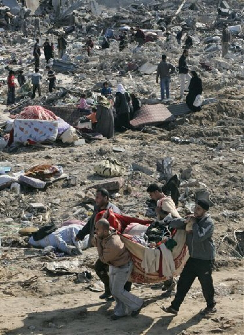Palestinians inspect the rubble of buildings in the eastern area of Jebaliya after Israeli troops withdrew in the northern Gaza Strip, Sunday, Jan. 18, 2009. Israel troops in the Gaza Strip were ordered to hold their fire early Sunday after Israel announced a unilateral cease-fire meant to end thre