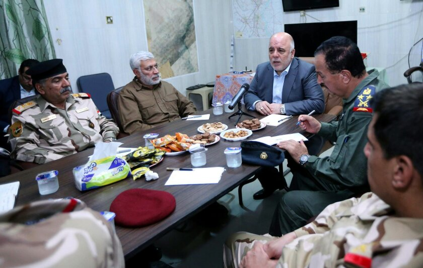 In this Monday, Aug. 24, 2015 photo, Iraq's Prime Minister Haider al-Abadi, second from right, meets with his military commanders at an Iraqi Army base near the oil refinery town of Beiji north of Baghdad, Iraq. Al-Abadi said that winning the ongoing battle over control of an oil refinery town north of Baghdad is the key to defeating the Islamic State group in Iraq during his visit to the town of Beiji. (AP Photo)