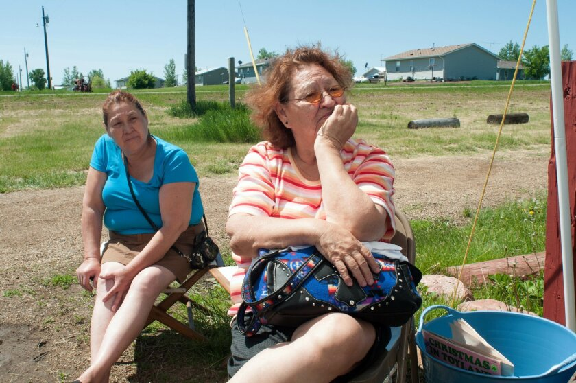 In this June 9, 2014 photo Alma Thunder Hawk, right, and Bernetta Thunder Hawk sit at a yard sale on the Standing Rock Indian Reservation in Cannon Ball, N.D. When Alma Thunder Hawk moved back to the reservation some 50 years ago, there's wasn't room for her family so she, her parents and six relatives lived in a tent on the North Dakota prairie. Now, with her government-issued trailer uninhabitable, Thunder Hawk moves from house to house among friends in Cannon Ball, the Native American community of less than 1,000 that President Barack Obama will visit Friday. (AP Photo/Kevin Cederstrom)