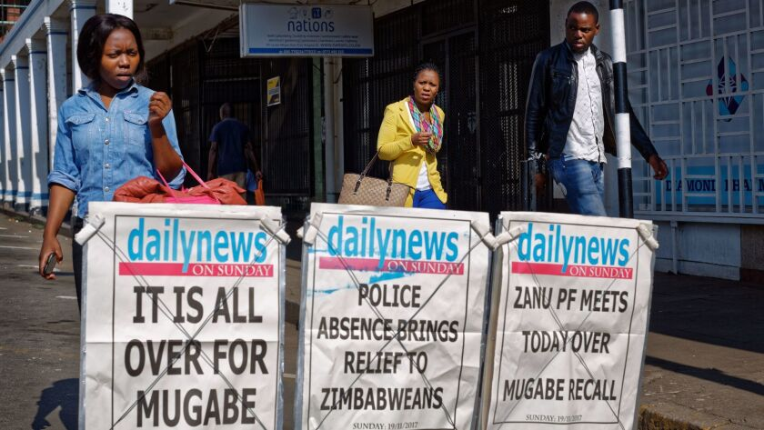 Pedestrians walk past a newspaper stand on a street in downtown Harare, Zimbabwe Sunday, Nov. 19, 20