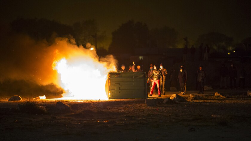 Migrants set trash bins alight during a protest at the makeshift camp Oct. 23.