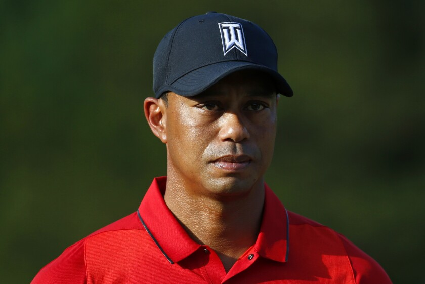 Tiger Woods takes part in a trophy ceremony for his Quicken Loans National on June 26.
