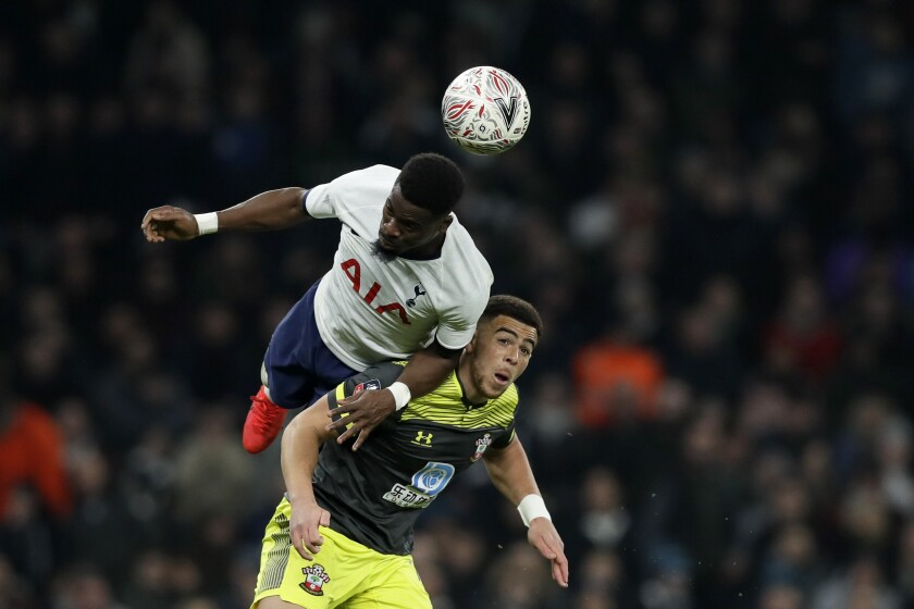 Tottenham's Tanguy Ndombele heads the ball above Southampton's Jan Bednarek, right, during the English FA Cup fourth round replay soccer match between Tottenham Hotspur and Southampton at the Tottenham Hotspur Stadium in London, Wednesday, Feb. 5, 2020. (AP Photo/Kirsty Wigglesworth)