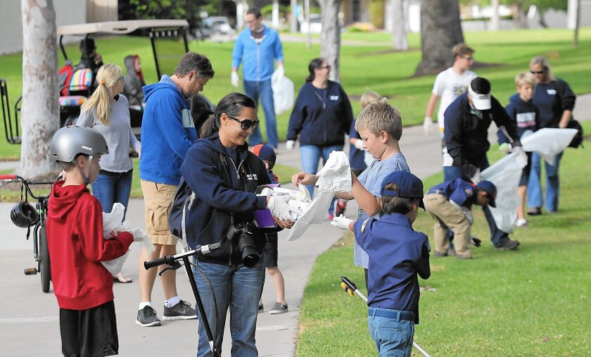 Organizer Carol Lewis hands out trash bags and rubber gloves to neighborhood kids during the first Port Streets HallowClean effort to pick up Halloween trash in the neighborhood's greenbelt area.