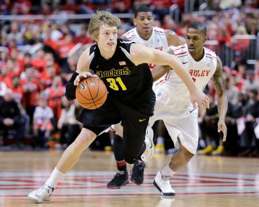 Wichita State guard Ron Baker (31) pushes down the court past the defense of Bradley guard Ka'Darryl Bell (0) during the first half of an NCAA college basketball game at Carver Arena, Tuesday, Feb. 25, 2014, in Peoria, Ill. (AP Photo/ Stephen Haas)