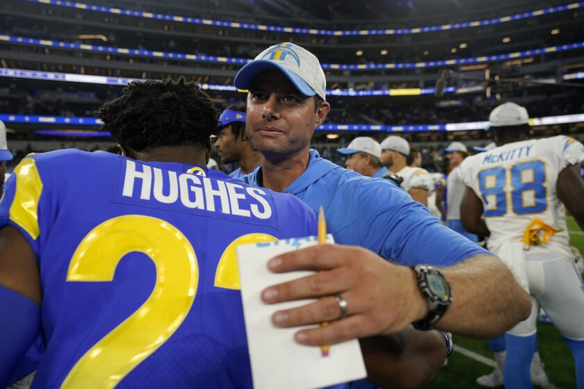 Chargers head coach Brandon Staley, right, hugs  Rams defensive back JuJu Hughes after a preseason game.