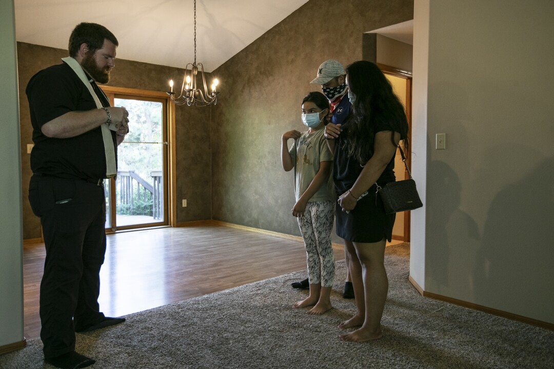 The Rev. Kristopher Cowles prays with the Centeno family, Abby, Abe and Astrid, inside their newly purchased home.