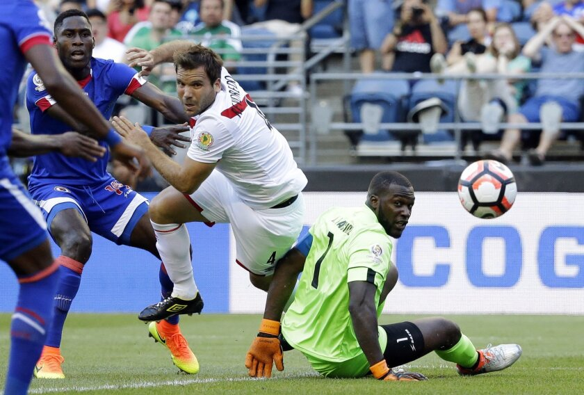 Haiti goalkeeper Johnny Placide, right, eyes the ball as he goes down and Peru defender Renzo Revoredo (4) battles with Haiti midfielder Sony Norde, left, in the second half of a Copa America Centenario soccer match Saturday, June 4, 2016, in Seattle. Haiti was able to clear the ball on the play an
