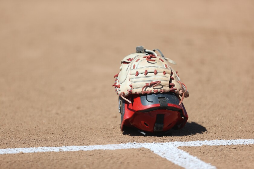 A softball catcher's helmet and glove on the field.