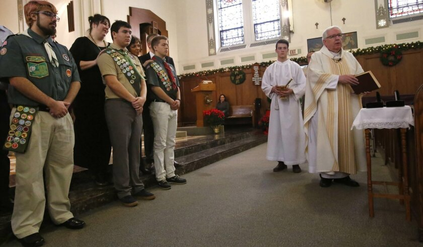 A priest blesses Boy Scout Eagle awards during a Catholic Mass in Chicago on Sunday, Jan. 3, 2016. David Fite, flanked by other scouts, was among those who received the Eagle rank at the service. (AP Photo/Martha Irvine)