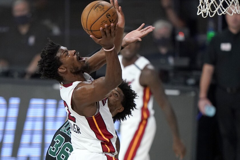 Miami Heat's Jimmy Butler, front, goes up for a shot over Boston Celtics' Marcus Smart, rear, during the first half of an NBA conference final playoff basketball game, Tuesday, Sept. 15, 2020, in Lake Buena Vista, Fla. (AP Photo/Mark J. Terrill)